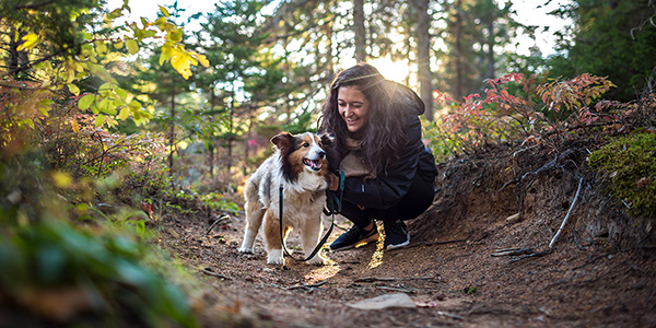 A woman and her dog enjoying the Major Kollock Trail in Kouchibouguac National Park.