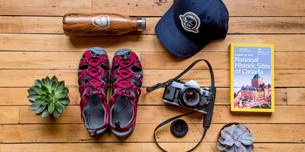 An arrangement of gear including a water bottle, cap, sandals, camera and travel guide.